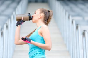 39503640 - portrait of healthy fitness girl drinking protein shake. woman drinking sports nutrition beverage while working out